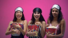 有眼罩的大声笑三个的女孩吃玉米花和,滑稽的喜剧 影视素材
