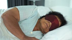 有眼罩的资深妇女睡觉在床上的 股票录像