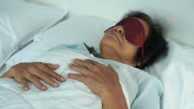 有眼罩的资深妇女睡觉在床上的 股票视频