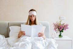 有眼罩的迷人的年轻女人在她的顶头读书时尚在床上 与花束,警报的卧室装饰 库存照片