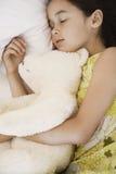 有睡觉在床上的玩具熊的女孩 库存图片