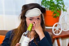 有睡觉眼睛mak的醉酒的妇女在她的头和拿着一个瓶酒精和做令人厌恶的面孔,宿酒 免版税库存照片