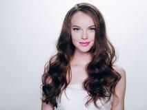 有睫毛引伸和长的深色的卷曲发型粉色口红的美丽的深色的妇女 免版税库存图片