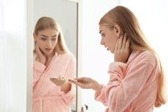 有睫毛损失问题的妇女在镜子附近户内 免版税库存图片