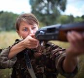 有瞄准目标的枪的女孩 免版税库存图片
