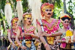 有矛的未认出的人在五颜六色的巴厘语战士服装 免版税库存照片