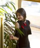 有短发的一个女孩在有红色口红的一件黑礼服 免版税库存图片