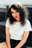有短发的卷曲美丽的深色的女孩在一个木楼梯的白色无袖衫 图库摄影