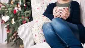 有短发的年轻美丽的妇女享用茶的,坐在圣诞树前面 地道家庭xmas 免版税图库摄影
