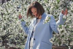 有短发的美丽的微笑的深色的女孩在一件蓝色外套在有樱桃树的一个用花装饰的春天庭院 树是cov 图库摄影