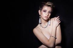 有短发的美丽的性感的肉欲的女孩有裸体明亮的构成的,美丽的晚上首饰耳环,项链, b 免版税库存照片