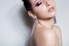 有短发的美丽的性感的肉欲的女孩有裸体明亮的构成的,美丽的晚上首饰耳环,项链, b 免版税库存图片