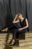 有短发的金发碧眼的女人在有鞋带袖子和凉鞋的蓝色总体与高跟鞋 图库摄影