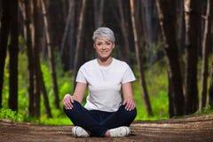 有短发的,休息的坐女孩金发碧眼的女人在一个年轻,美丽,微笑的女孩的冷杉森林画象, 库存图片