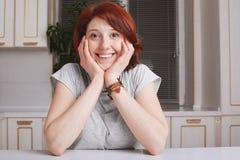 有短的姜头发的快乐的喜悦的女性看与愉快的表示照相机,保留在面颊的手,穿戴随便,坐 免版税库存图片