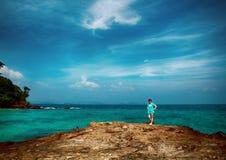 有短的棕色头发的一名妇女在海滩站立 夏天,热 海是美丽的蓝色 对岩石岸的波浪奔跑 库存图片
