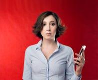 有短的理发的一年轻女人在在手中和镇静地拿着电话的红色背景的一件蓝色办公室女衬衫 免版税库存图片