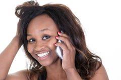 有短的理发的年轻可爱的非洲妇女谈话在手机与她的朋友 库存图片