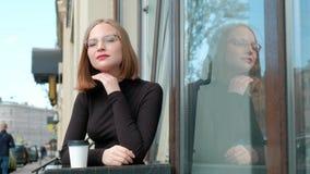 有短的理发,一四方的可爱的红发年轻女人,与玻璃和棕色高领衫,坐  股票录像