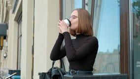 有短的理发,一四方的可爱的红发年轻女人,与玻璃和棕色高领衫,坐  股票视频