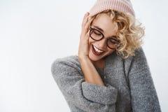 有短的白肤金发的时髦的发型的嫩感情和无忧无虑的行家女孩在桃红色冬天童帽和毛线衣接触 库存照片