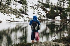 有短的看山的全景和放松在前面的气喘美国国旗的远足者对瓦尔d `的奥斯塔一个沈默湖 免版税库存照片