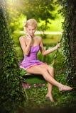 有短的礼服的美丽的金发碧眼的女人和创造性的理发在庭院摇摆 免版税库存图片