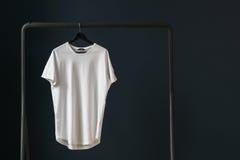 有短的袖子的T恤杉在以黑暗的墙壁为背景的一个挂衣架 免版税库存照片