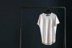 有短的袖子的T恤杉在以黑暗的墙壁为背景的一个挂衣架 库存照片