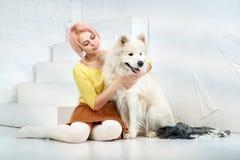 有短的金发的可爱的女孩在一条黄色毛线衣和裙子拥抱她心爱的宠物-狗品种萨莫耶特人 免版税库存照片