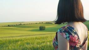 有短的黑发的美丽的欧洲女孩在与站立在与他的照相机前面的花的短裙  影视素材