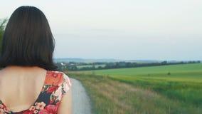 有短的黑发的美丽,可爱的欧洲女孩在与花的短裙沿有石渣的,背面图路走, 股票视频