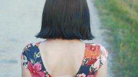 有短的黑发的美丽,可爱的欧洲女孩在与花的短裙沿有石渣的,背面图路走 股票录像