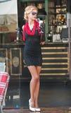 有短的黑鞋带礼服和红色围巾和高跟鞋的,室外射击时兴的夫人 年轻可爱的短发金发碧眼的女人 免版税库存图片