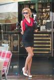 有短的黑鞋带礼服和红色围巾和高跟鞋的,室外射击时兴的夫人 年轻可爱的短发金发碧眼的女人 图库摄影