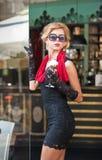 有短的黑鞋带礼服和红色围巾和高跟鞋的,室外射击时兴的夫人 年轻可爱的短发金发碧眼的女人 免版税库存照片