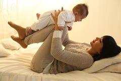 有短的黑发和她的小逗人喜爱的男婴的美丽的母亲 免版税库存照片