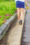 有短裙的女孩在花园里走 免版税库存图片