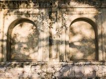 有石凹室的老与阳光的墙壁和凹进处在佛教寺庙 免版税图库摄影