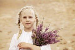 有石南花花的逗人喜爱的儿童女孩 免版税库存图片