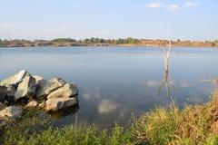 有石和死的树的岩石湖 免版税库存图片