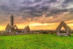 有石塔的Kilmacduagh修道院在日落 免版税库存图片