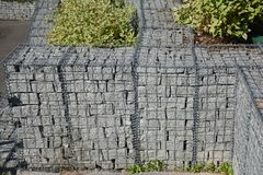 有石头的现代gabion篱芭墙壁在庭院设计的铁丝网 Gabion操刀与自然石头的铁丝网 免版税库存照片