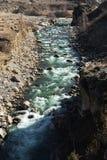 有石头的风雨如磐的山河飞溅和泡沫与鲜绿色颜色清楚的饮用水  概念的自然 库存图片