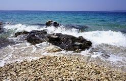 有石头的Pebble海滩、海泡沫和蓝色和绿松石海和天空在背景中 免版税库存照片