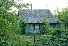有石板屋顶的老房子在一个绿色庭院里 免版税库存照片