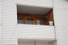 有石棉屋顶、舒适阳台和支持的门面的修造的顶楼房子建筑 库存照片