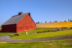 有石渣路和麦田的大型红色谷仓 库存照片