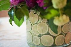 有石灰和花的花瓶反对一张白色桌布 免版税库存照片