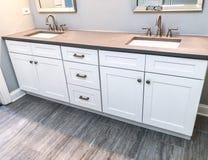 有石英工作台面、两个水槽和龙头的白色现代卫生间镜箱有石地板的 免版税库存图片